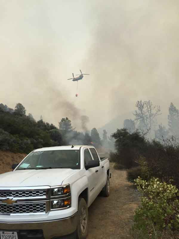 Helicopter dropping water on a wildfire.