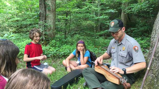 Powell Boys and Girls Club listen to mountain tales as Park Ranger Jared Ownby plays mountain music on the dulcimer. NPS Photo.