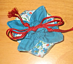 "Small pouch to hold a gift of handmade bracelets and earrings, made from 8"" squares."