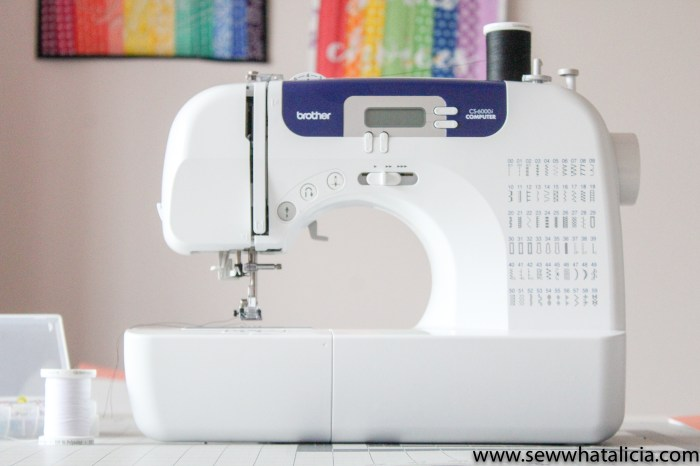 Pictured Brother CS6000i sewing machine. Rainbow quilts blurred in background on the wall.