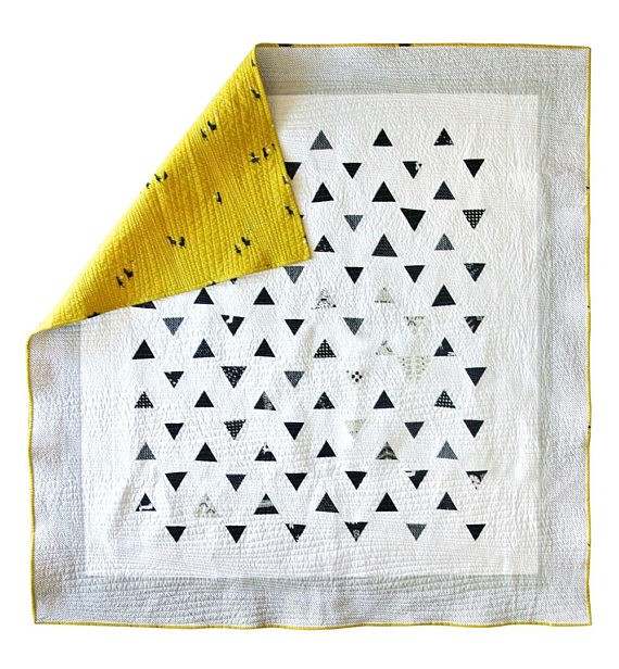 pictured white quilt with black triangles and a yellow back corner folded over
