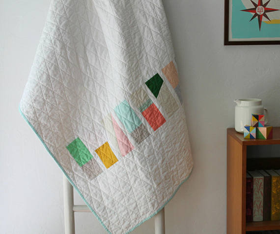pictured modern quilt hanging on quilt ladder