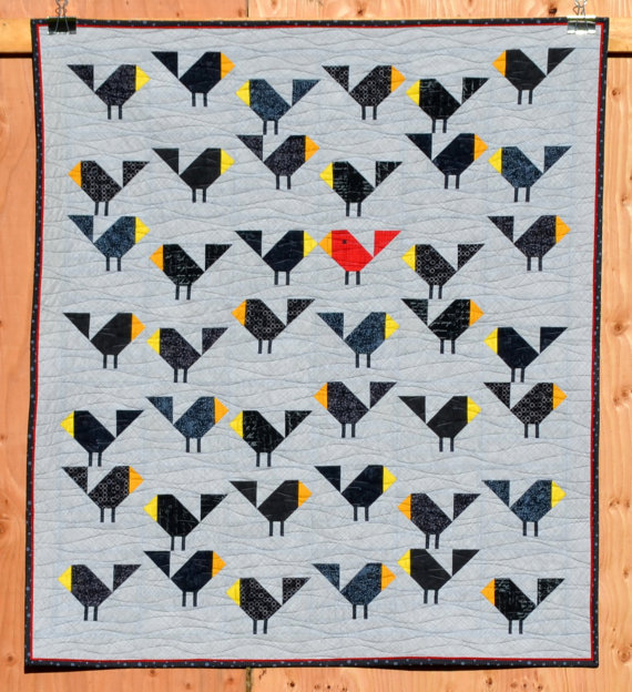 pictured quilt with black birds hanging on a wooden backdrop