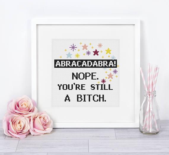 pictured cross stitch framed that reads abracadabra nope you're still a bitch