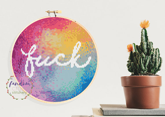pictured rainbow cross stitches covering an entire hoop with word fuck in white