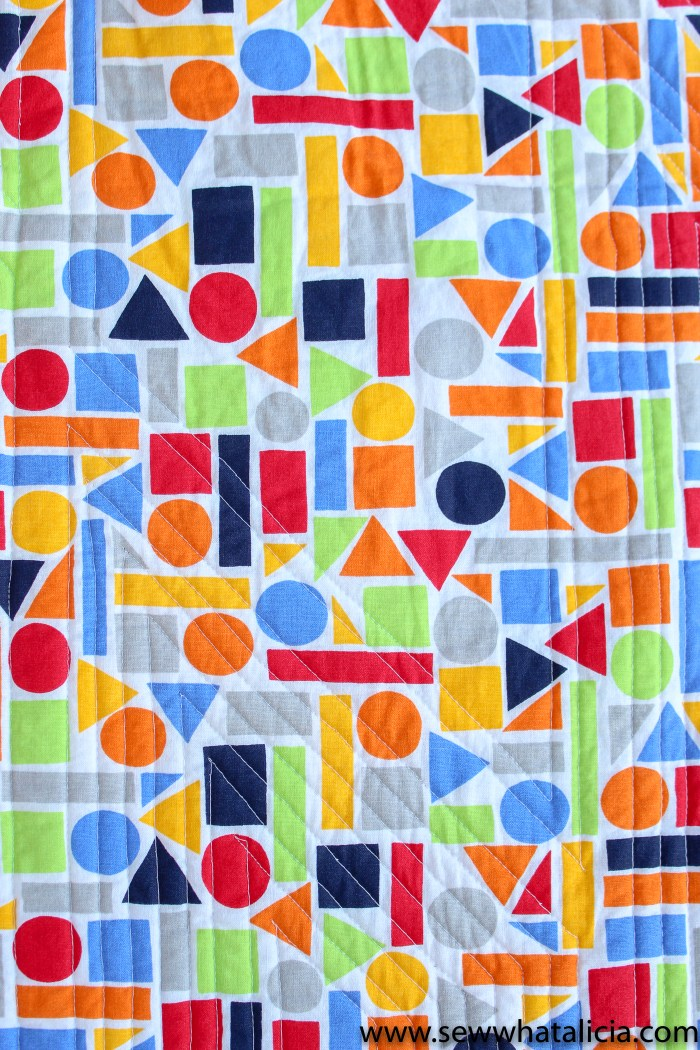 Scrappy Easy Rainbow Quilt Pattern and Tutorial: Pictured back of quilt with straight line quilting evident. | www.sewwhatalicia.com