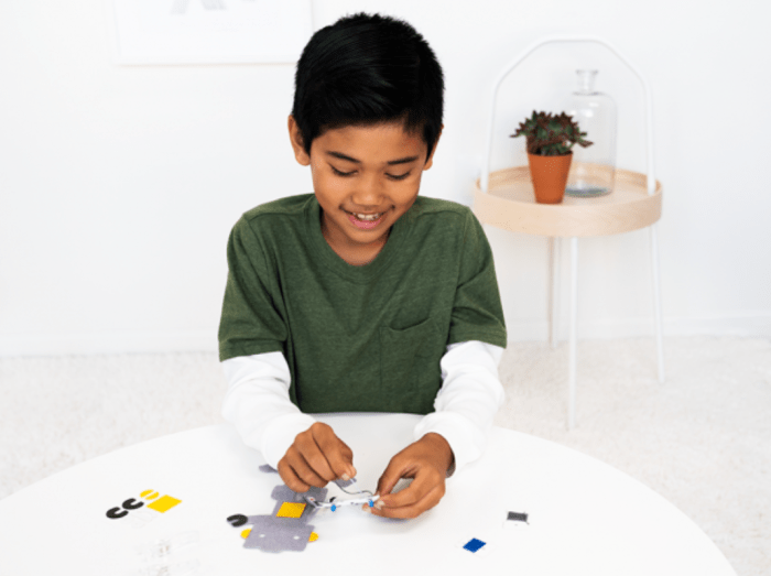 pictured young boy sewing robot circuit