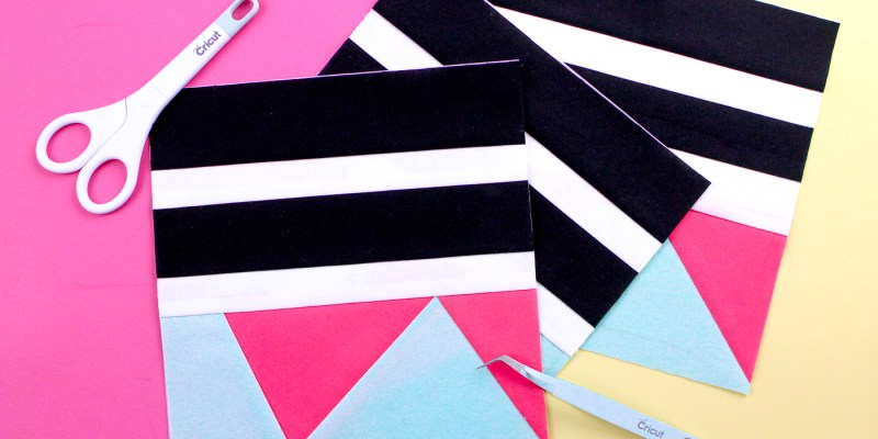 Pictured three quilt blocks in white, black, pink, and aqua. Scissors and tweezers.