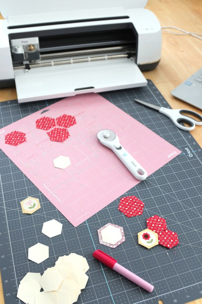 pictured Cricut Maker, pink cutting mat, hexagons, and a rotary cutter