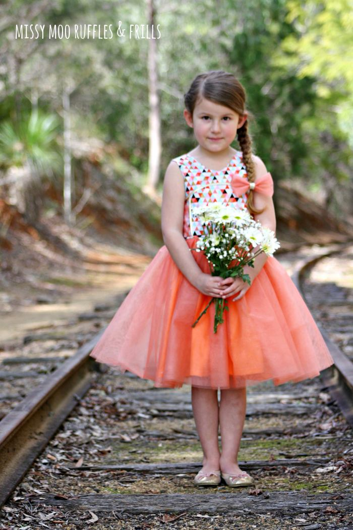 pictured girl in azure party dress holding flowers