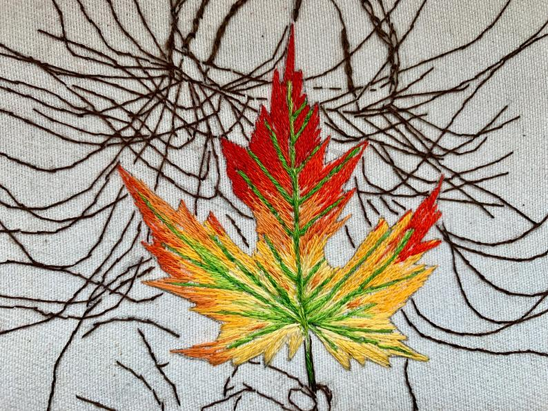 embroidered bright fall leaf in outline of hand with wind blown hair