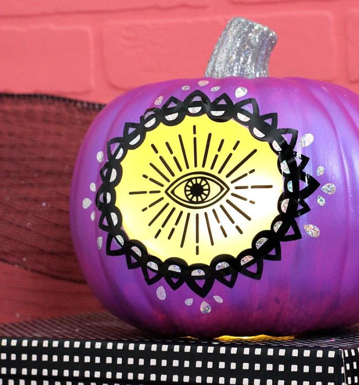 craft pumpkin painted purple with glowing eye