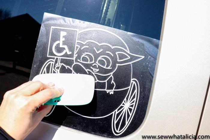 pictured scraper pressing the vinyl image onto the car door window