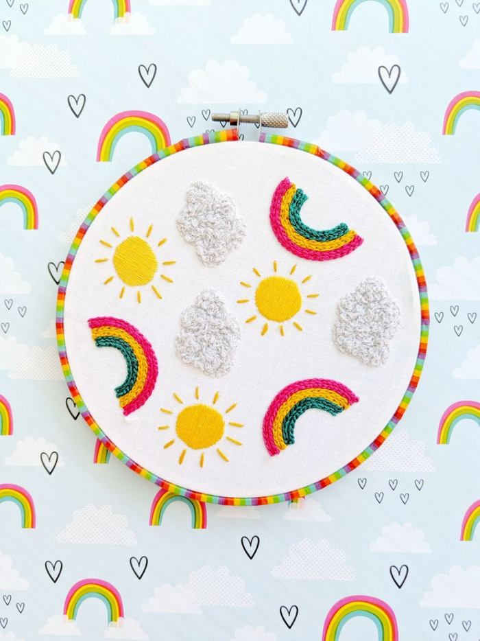 pictured rainbows, suns, and clouds embroidered on white fabric