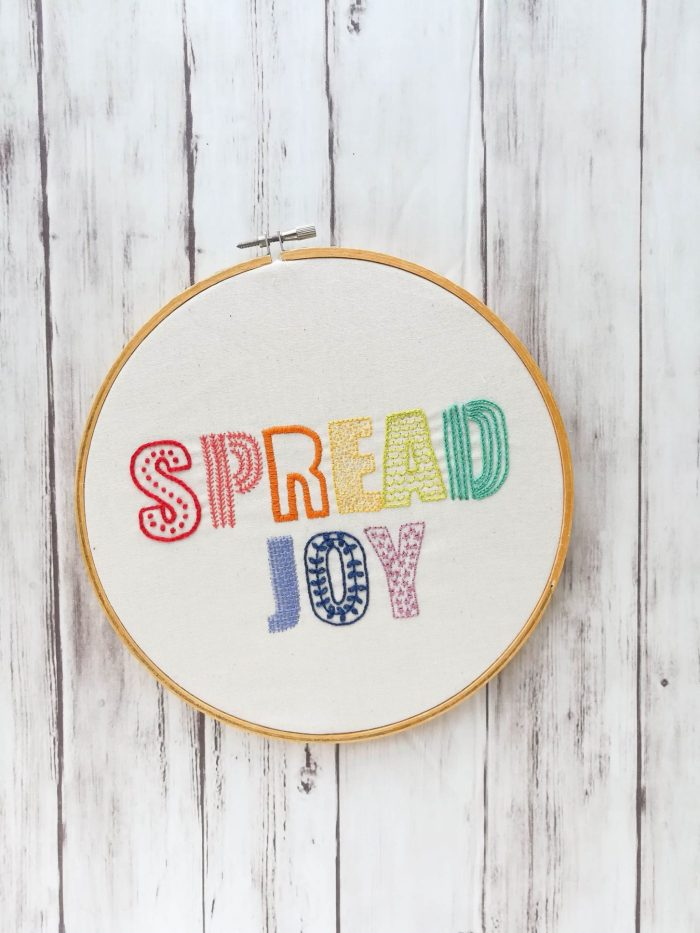 pictured the words spread joy done in rainbow colors and various stitches