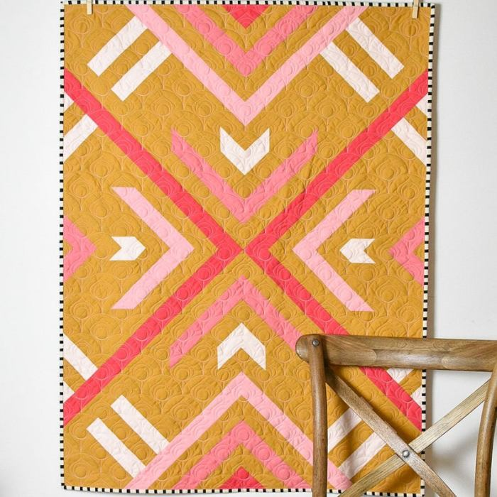 quilt hanging on wall next to a chair