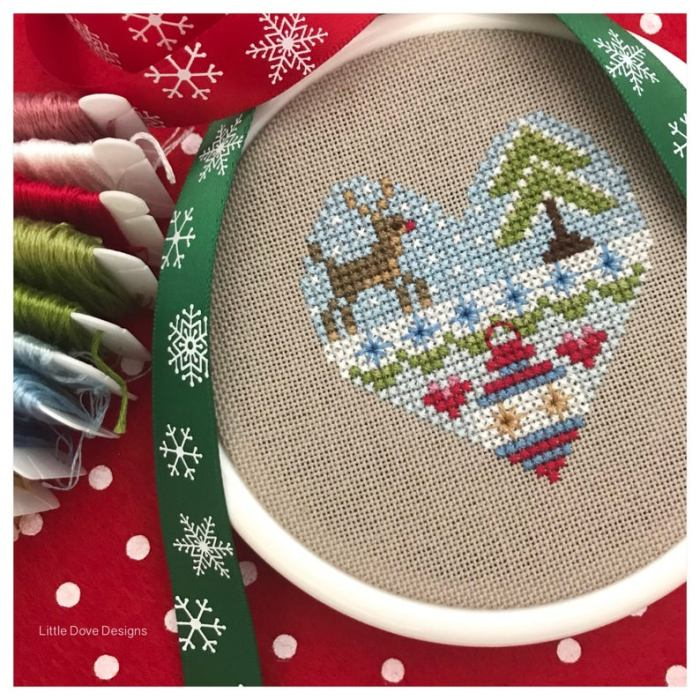 heart filled with holiday images done in cross stitch