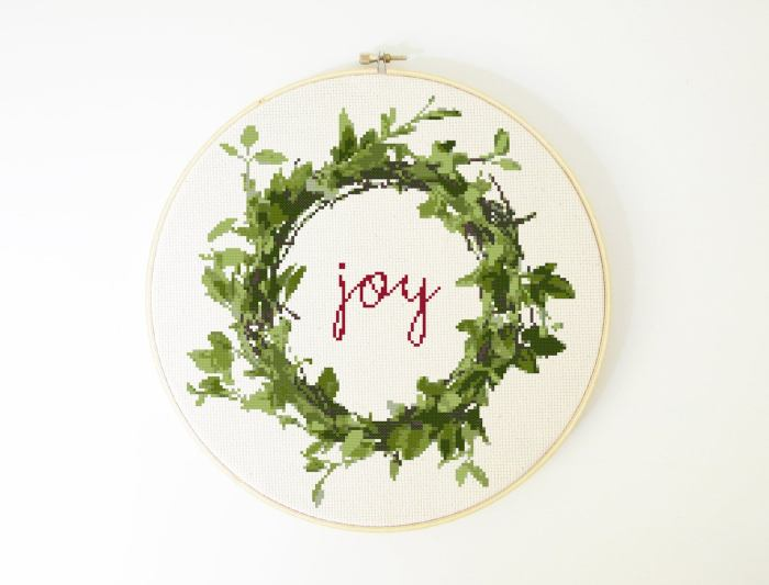 cursive joy written inside a green foliage wreath