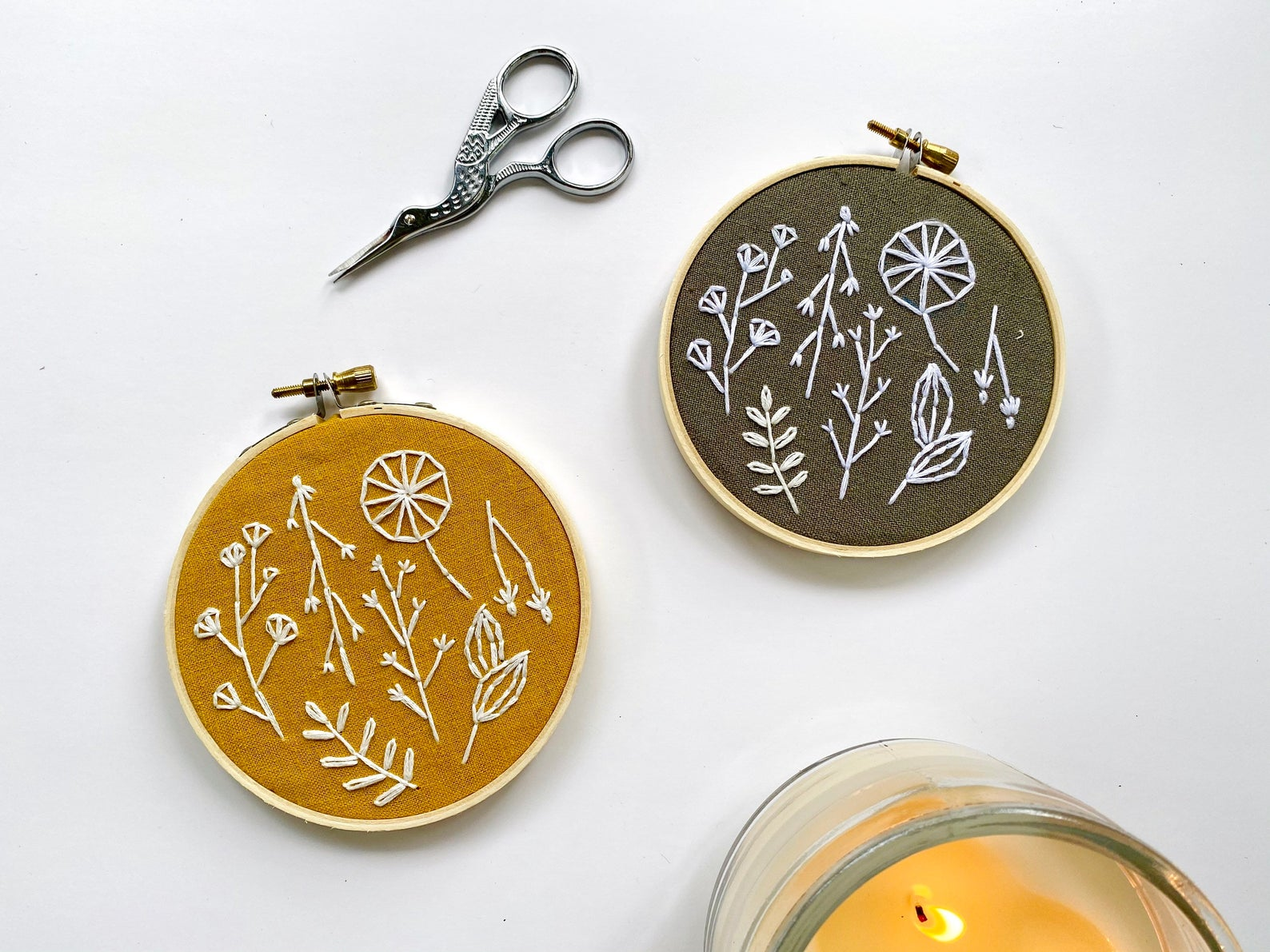 two finished embroidery hoops with embroidery scissors lying next and a burning candle