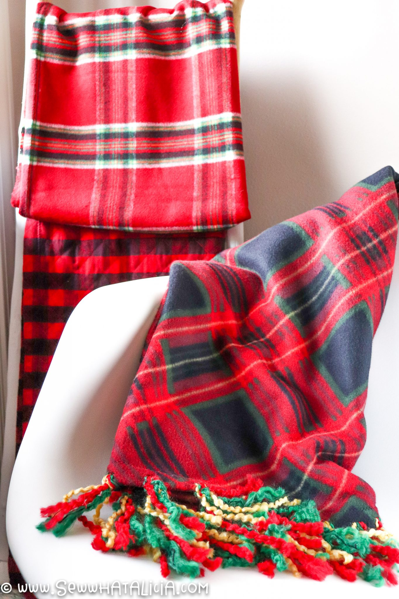 fleece blanket with fringe on white chair with plaid blankets on ladder in background