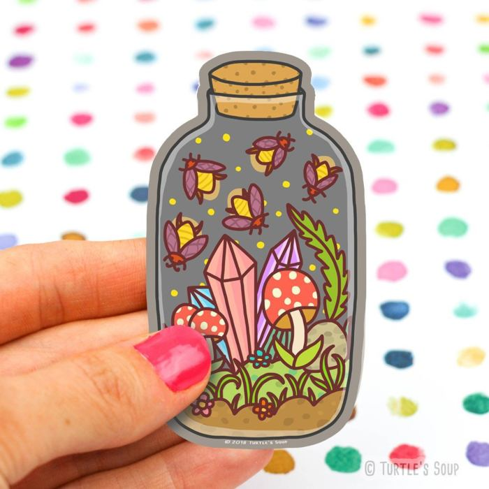 hand holding sticker featuring mushrooms, fireflies, and crystals inside a stoppered jar