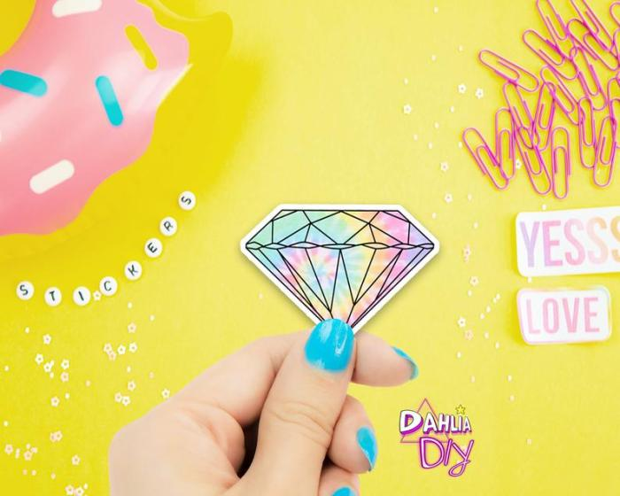 hand holding pastel tie dye diamond sticker with yellow background