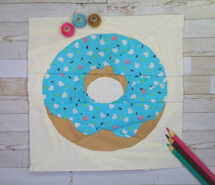 paper pieced donut with wood board background