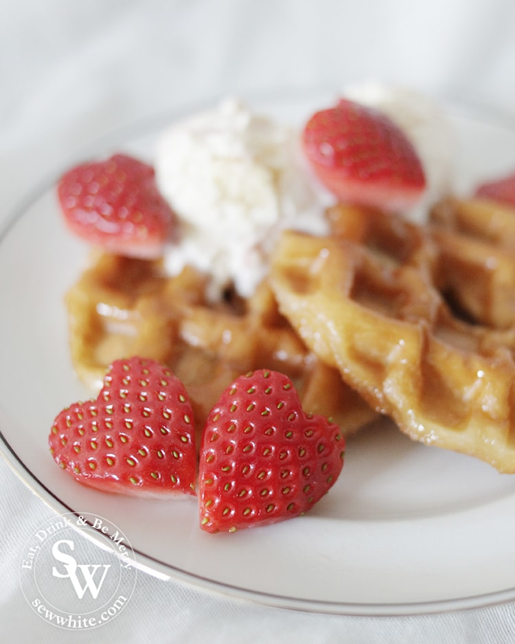 heart shaped strawberries served on a plate of hot doughnut waffles
