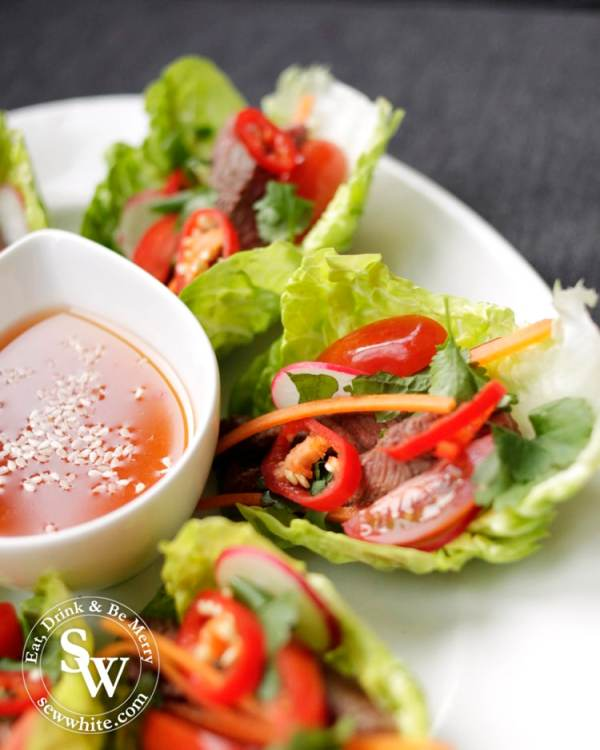Vietnamese Inspired Beef Salad Bites serving, the bright colurs of the tomatoes, chillies, carrots and green herbs make it very appetising.