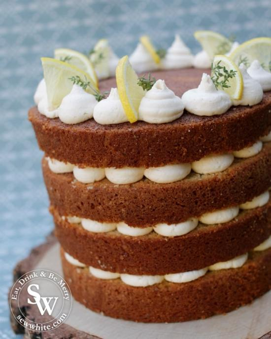 Close up of a naked cake with buttercream centre and decorated with lemon and thyme
