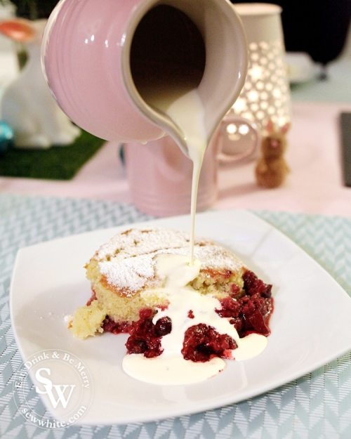 Pouring cream over the summer fruit sponge pudding. The rich red berries and golden sponge glisten on the plate.