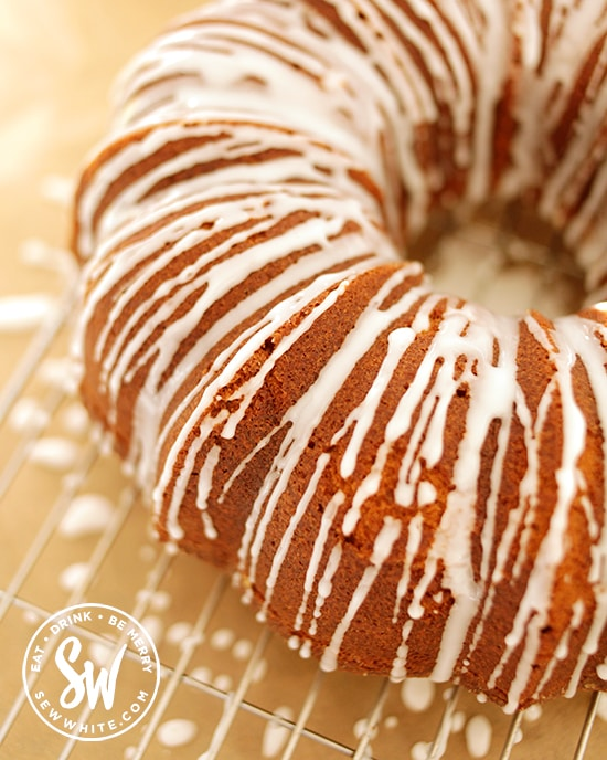 drizzling white icing over the bundt cake