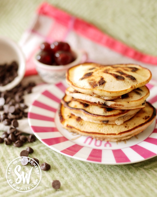 Stack of Chocolate Cherry Pancakes on a pink plate surrounded by glacé cherries and chocolate chips.