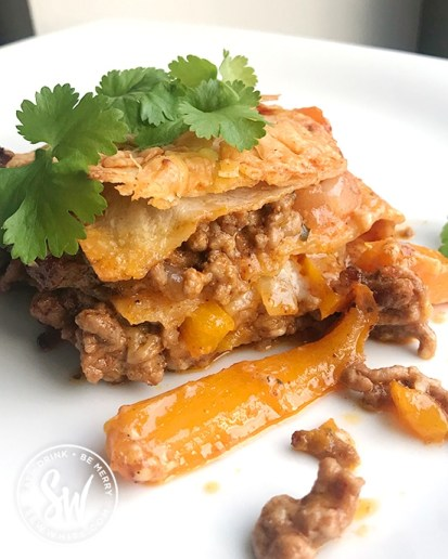 Fajita Traybake with visible layers or tortilla, peppers, been mince and onions. Mexican Lasagne topped with fresh coriander