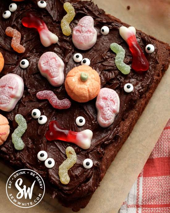 Easy Halloween Traybake with chocolate icing and chocolate frosting covered with sweets.