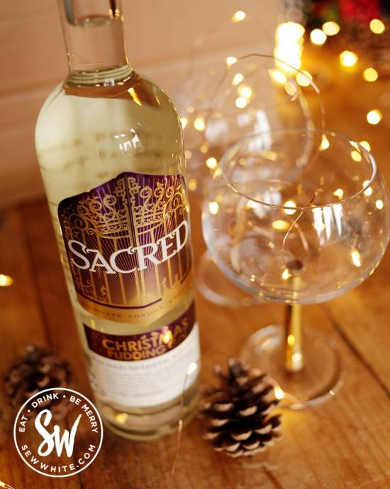 Scared Christmas pudding gin in time for Christmas made with whole Christmas puddings next to golden gin and tonic bowl glasses with fairy lights in the drink gift guide