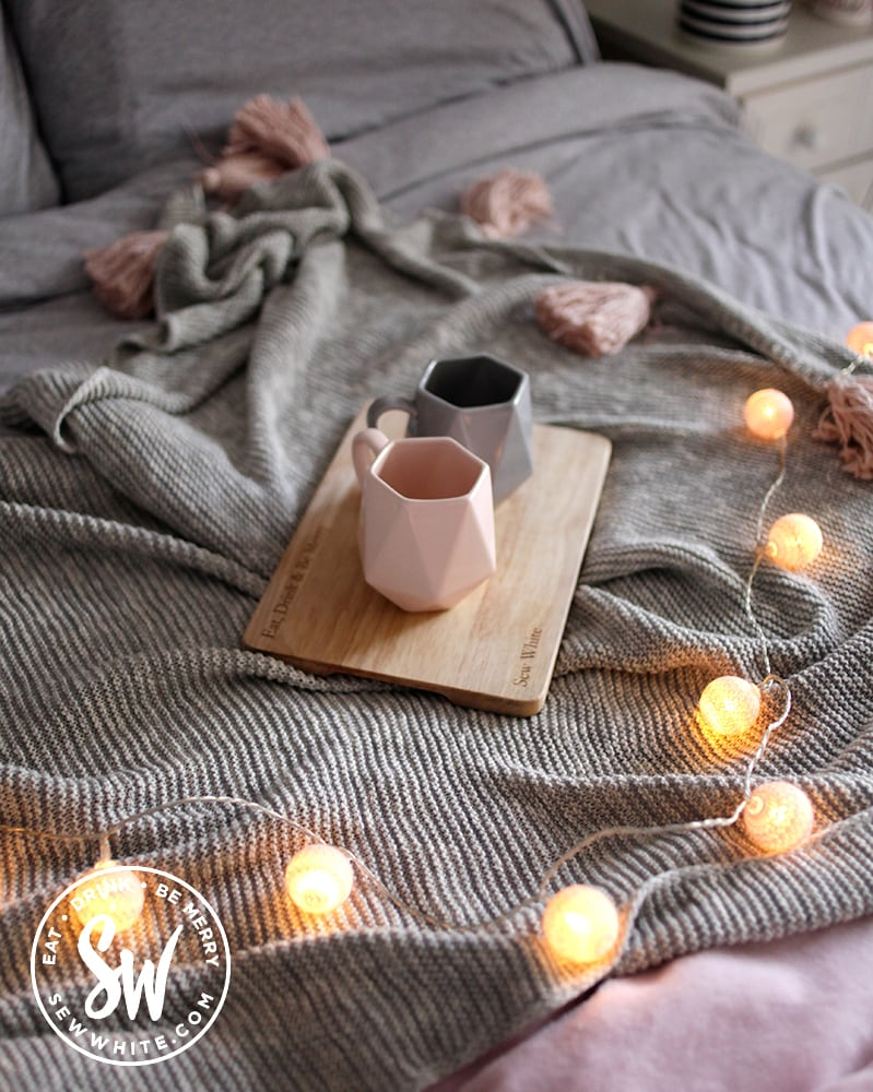Cups of tea on a tray on a grey blanket on a bed with fairy lights.