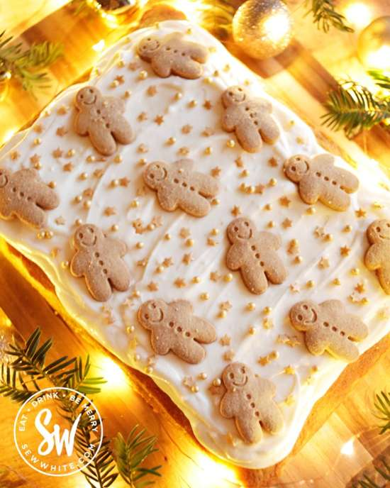 Gingerbread traybake decorated with cream cheese frosting and decorated with gingerbread men biscuits on a wooden board