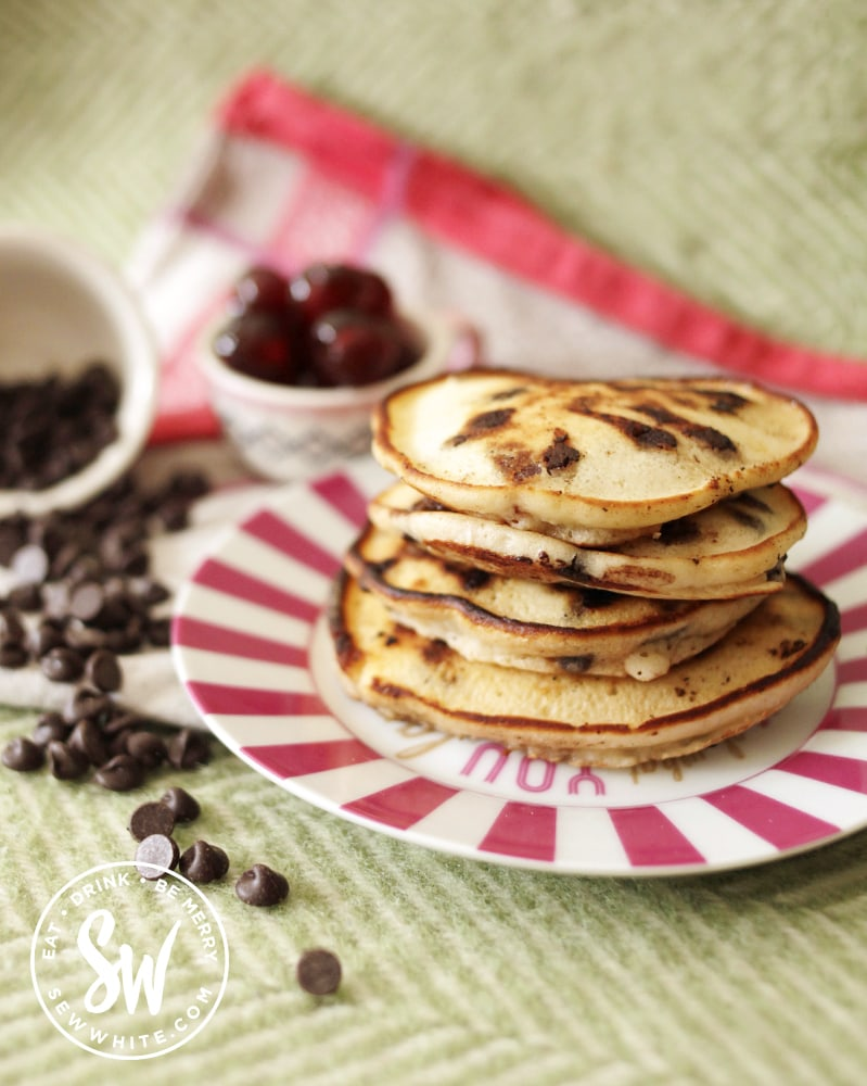 Easy cherry chocolate pancakes stack on a pink plate.