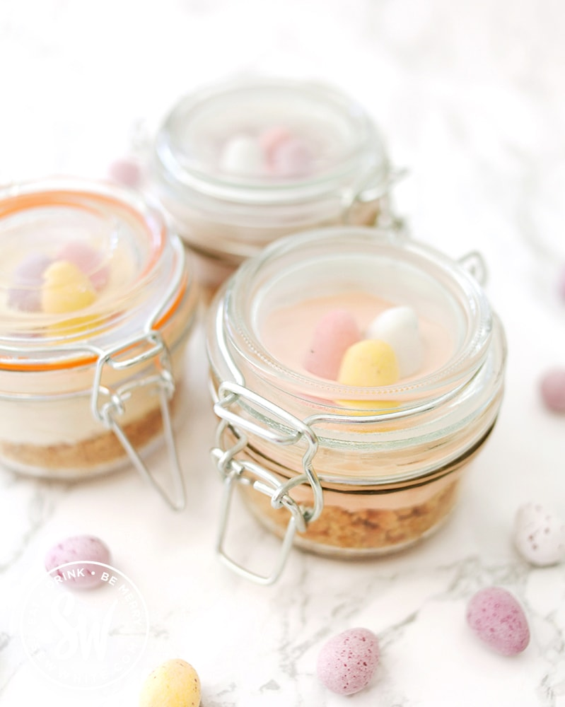 individual mini egg cheesecakes in kilner jars surrounded by mini eggs