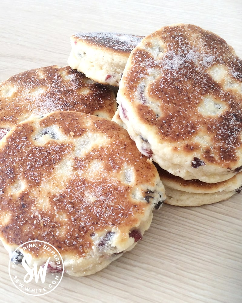 Cranberry and Lime Welsh Cakes dusted in sugar and ready to serve on a wooden board