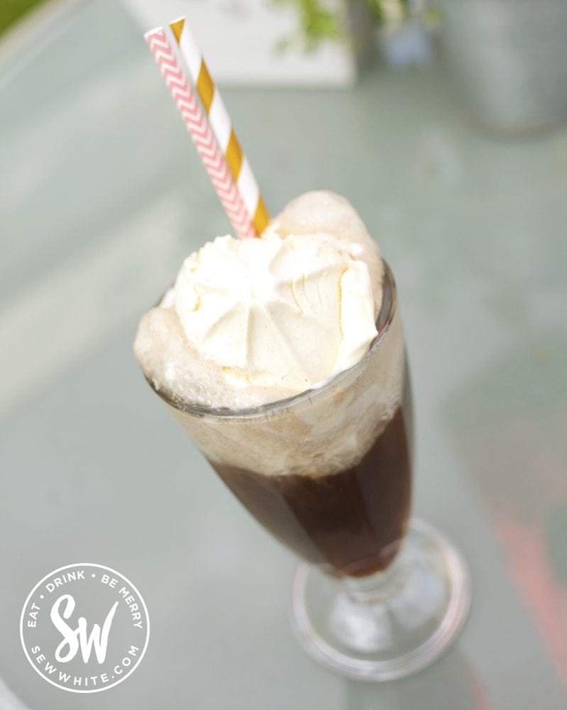 A big scoop of vanilla ice cream in a glass of coca cola to make an ice cream cocktail.
