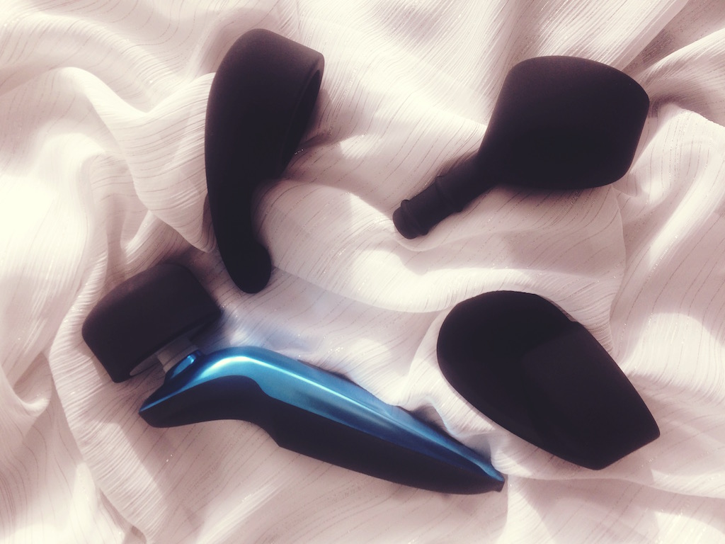 Tantus Rumble blue and black wand vibrator on white background side view with 3 other attachments