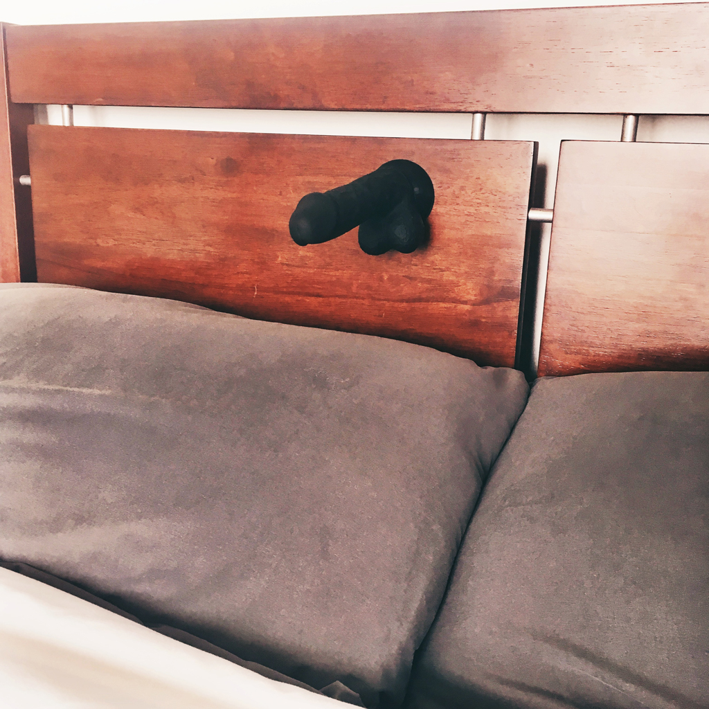 view of cloud9 dildo suctioned to bedroom headboard