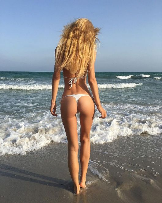 bikini-clad blode walking away into the surf