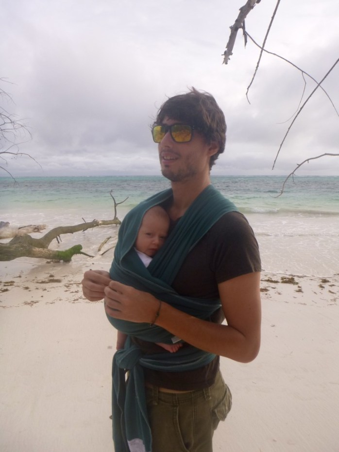 Family walk on the beach Praslin Seychelles. Daddy and baby. Baby wearing
