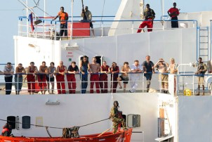 The crew of the hijacked Ukrainian merchant vessel MV Faina stand on the deck under the watch of armed Somali pirates looking as relaxed as if they were one big happy family on Nov. 9, 2008, after a U.S. Navy request to check on their health and welfare, at sea off the coast of Somalia. The Faina, loaded with Russian tanks and artillery, had been seized by the pirates in September. The pirates have never harmed anyone on the ships they've seized. – Photo: HO/AFP/Getty Images