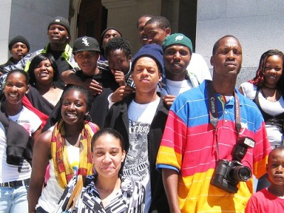 JT the Bigga Figga, rapper and activist, poses with scholars on the steps of the State Capitol in Sacramento after he spoke at the podium. – Photo: Francisco Da Costa