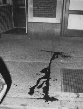 The official police crime scene photo also shows a clean trickle of blood on the pavement, not the splatter of blood or cement damage that one would expect from the firing of a .38 revolver. – Photo: Philadelphia Police Department