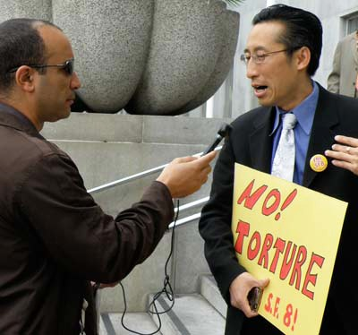 At the June 8 rally, Supervisor Eric Mar, right, announced he would introduce a resolution supporting the SF 8 by condemning the torture on which their case is based. The resolution puts him at great political risk because SFPD officers so badly want revenge against the men they accuse of killing one of their own that they have been pursuing the eight for 38 years. His is being interviewed by Max Pringle of KPFA.
